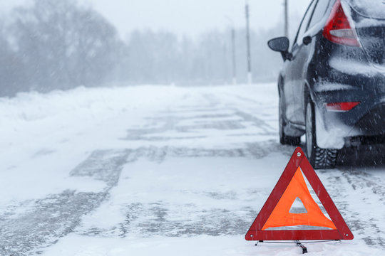 Closeup of red warning triangle with a broken down car in winter