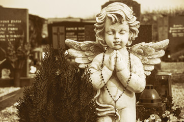 angel with folded hands and rosary on a churchyard