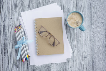 Cup of coffee,  colored pencils, glasses, notebook and white sheets of paper on grey wooden background