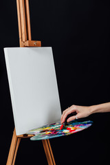 Cute beautiful girl artist painting a picture on canvas an easel. Space for text. Studio black background.