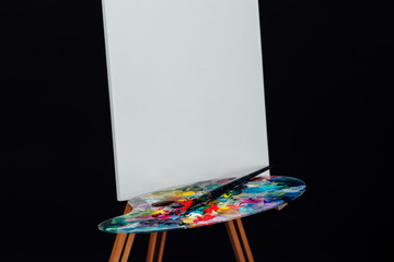 Tools of the artist. Brushes, wooden easel tripod, palette colorful. Black background, studio, nobody.