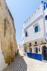 Stone alley with historic city wall and white and blue washed buildings in Asilah, Morocco, North Africa