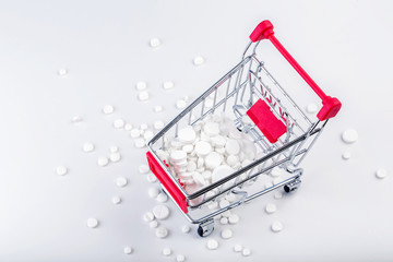 Bunch of white pills with shopping cart.