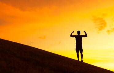Fit strong man flexing against a beautiful sunset.