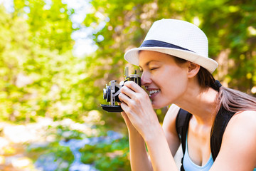 Female photographer taking pictures of nature using a classic film camera.