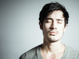 Young man thinking hard with eyes closed.