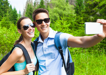 Couples traveling together concept. Happy young couple taking selfie in a green outdoor forest setting.