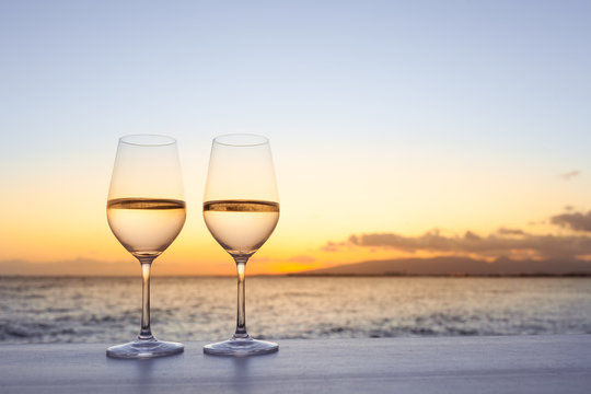 Pair of wine glasses on a bar at sunset.