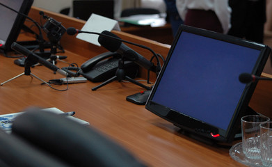 Press media conference studio with monitors, microphones on wooden table