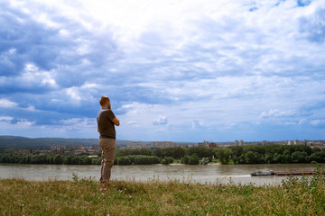 guy looking over river on the city.
