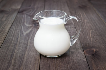 Milk in a glass jug on a wooden background.