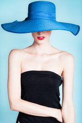 Fashion portrait of attractive woman wearing blue hat and red lipstick.