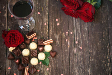 Old wooden background with red roses and chocolate pralines copy
