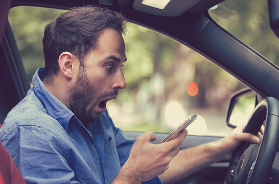 Man sitting inside car with mobile phone texting while driving