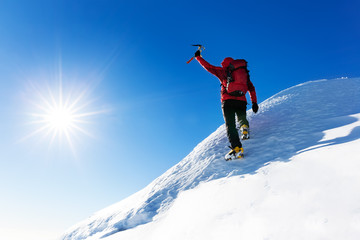 Foto op Aluminium Alpinisme Extreme winter sports: climber reaches the top of a snowy peak in the Alps. Concepts: determination, success, strength.