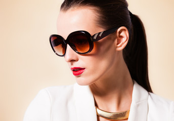 Fashion portrait of attractive female wearing sunglasses and red lipstick.