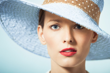 Beauty portrait of woman wearing hat and red lipstick.
