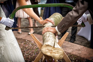 Bride and groom cutting wood log on wedding