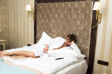 bearded man on bed with remote