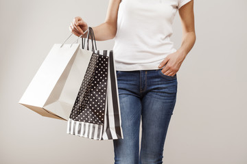 Woman holding paper shopping bags on gray background