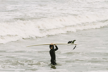Young man carries a surfboard as he leaves the sea on the shores