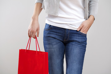 Woman holding paper shopping bag on gray background