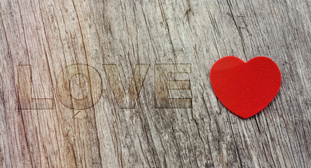 Red heart on wooden background vintage style with word LOVE