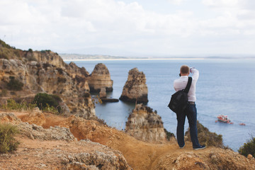 A young man photographing the ocean standing on the cliff Portugal Lagos