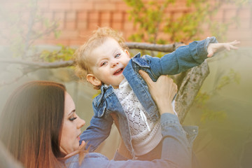 Mother and daughter in a spring park. They are having fun and playing. Girls dressed in denim jackets. Spring mood. Family time.