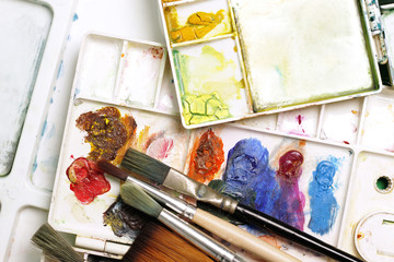 Artists brushes and watercolor paints on palette, Vintage of paintbrushes closeup and artist palette, stylized photo.