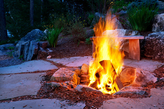Blazing fire in a fire pit on a Summer evening outside on a stone patio
