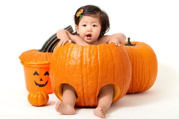Baby girl in giant pumpkin for Halloween