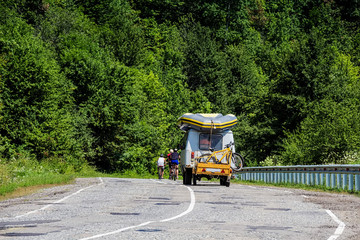 Cyclists on mountain road with support vehicle