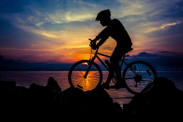 Healthy lifestyle. Silhouette of bicyclist riding the bike at seaside