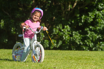 outdoor portrait of young happy child girl riding a bike in park