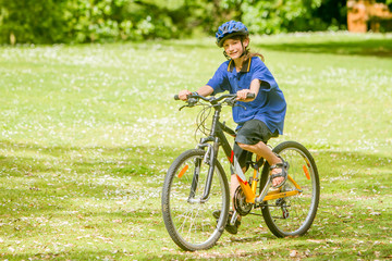 young happy preteen child boy riding a bicycle on natural park b