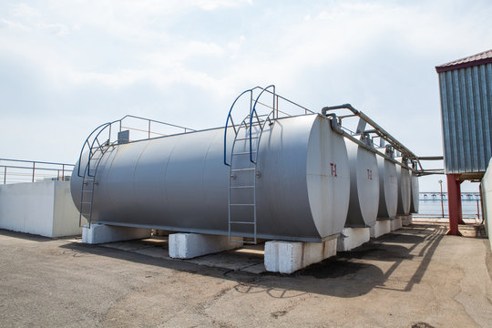 Huge oil, gas and liquid storage tanks in open air field at factory