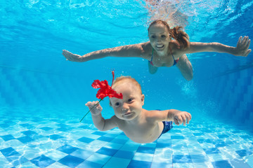 Family fitness - happy mother, active baby son learning swim, dive underwater with fun in pool. Active parents healthy lifestyle, water sport activities, kids aqua classes, children swimming lesson.