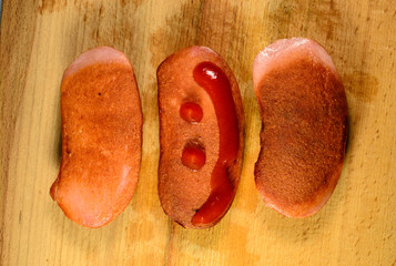 Sausages with ketchup on a wooden table