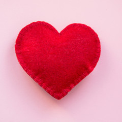 Valentine's day card. Red felt heart on white background. Top view.