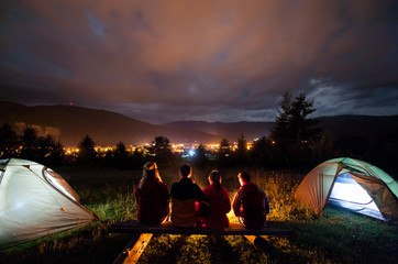 Silhouette of four people sitting on a bench made of logs and watching fire together beside camp and tents in the night on the background mountains and luminous town. Rear view
