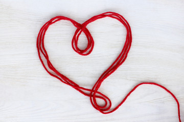 festive Valentine/ heart symbol of the red threads lying on a light wood surface top view