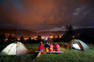 Friends sitting on a bench made of logs and watching fire together beside camp and tents in night on the background mountains and luminous town. Rear view