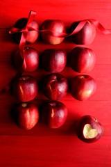 ハート型に皮を剥いた林檎とリボン 赤色背景