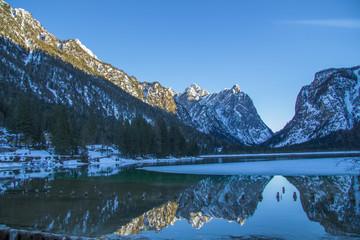 Photo sur Aluminium Reflexion Riflesso delle montagne innevate sul lago di Dobbiaco