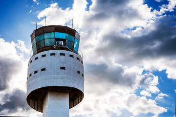 Modern airport control tower with cloudy sky behind