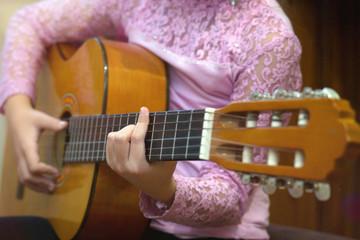 Девочка держит  гитару.
