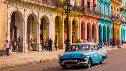 A blue oldtimer taxi is driving through Habana Vieja in front of a colorful facade