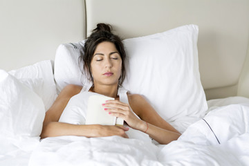 young tired woman  sleeping in white bed with book in the hands