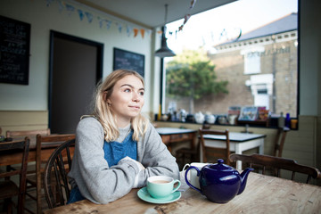 Young woman sitting in cafe, cup of tea and teapot on table, thoughtful expression